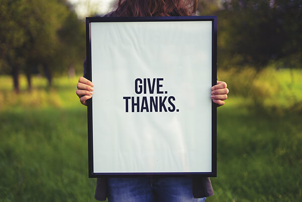 woman holding give thanks sign