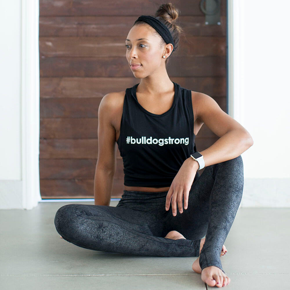 woman sitting cross legged on the floor in yoga clothing