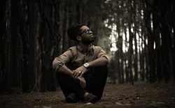 man wearing watch and glasses sitting in forest