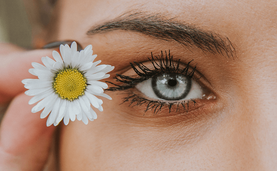 small daisy flower being held next to blue eye with mascara