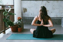 sitting woman with hands in reverse prayer yoga position