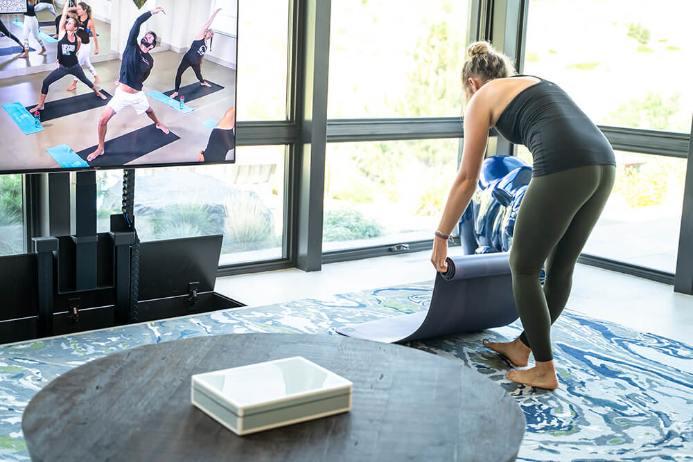 woman rolling out yoga mat to do an online yoga class