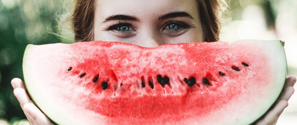 woman holding large slice of watermelon up to her face like a smile