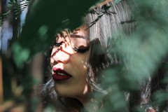 woman with eyes closed in shadows of leaves with sunlight