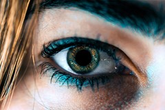 close up of blue eye surrounded by blue eyeliner