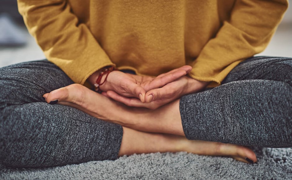 Closeup of persons hands and feet while meditating on gray carpet