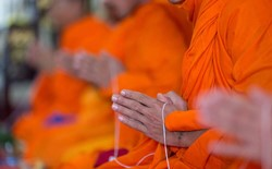 hands of Buddhist monks in orange robes praying