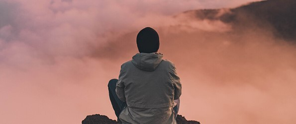 person in jacket and hat sitting on mountaintop above clouds