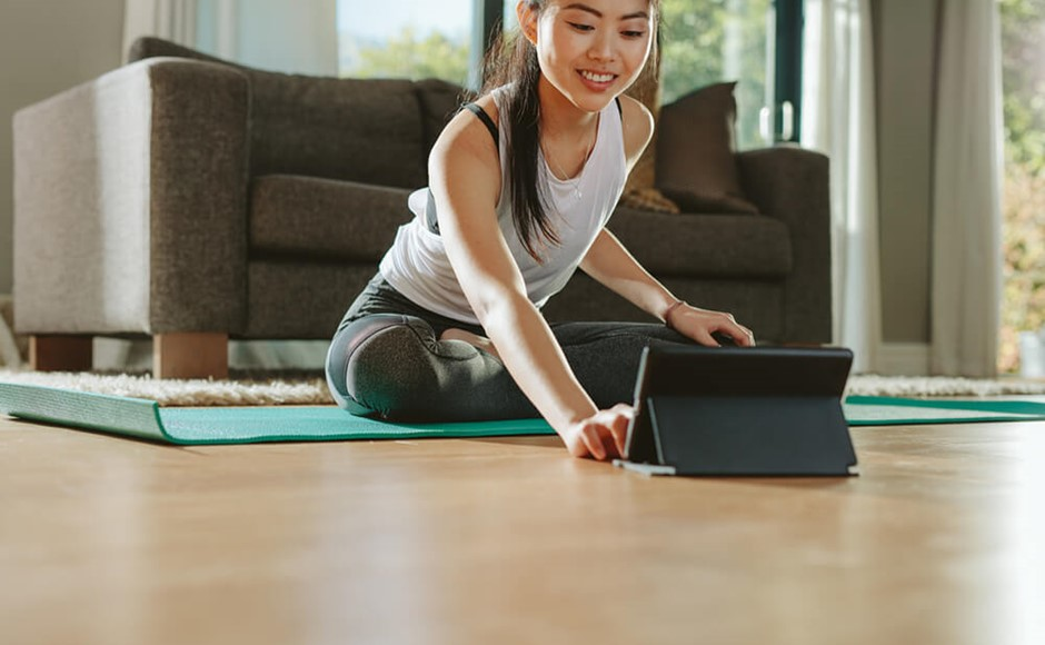 smiling woman sitting on yoga mat leans forward to use tablet