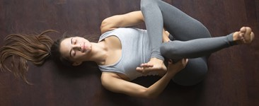 woman in gray doing yoga eye of the needle pose