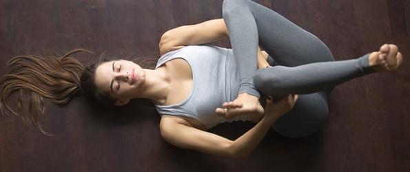 woman in gray doing yoga eye of the needle pose