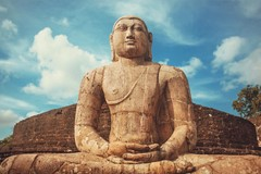 sand colored Buddha statue in front of brick wall with sky and clouds behind