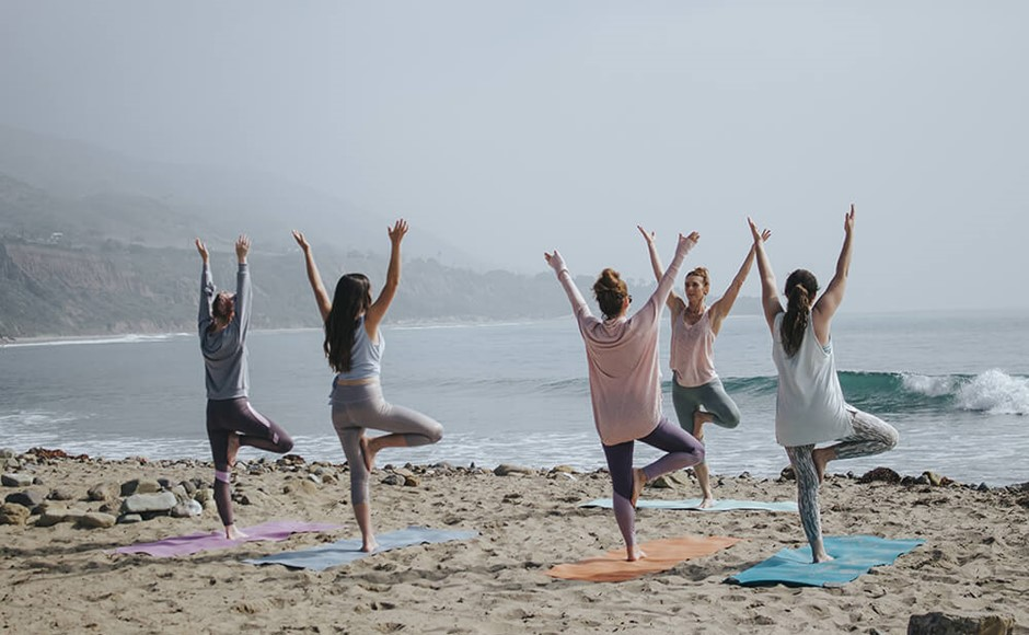 group of women in yoga tree pose on the beach on a cloudy day