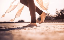 Lady in yoga legging walking across sand with bare feet