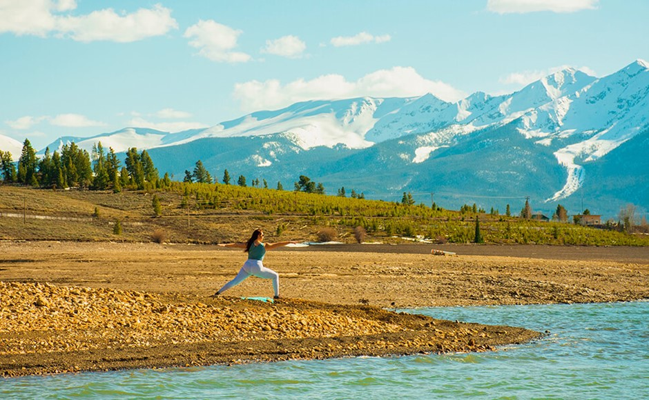 woman in warrior ii yoga pose next to river with mountains and trees in background