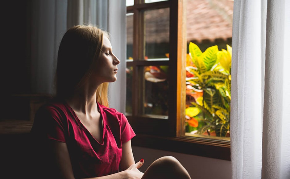 woman with eyes closed sitting next to open window with plants outside