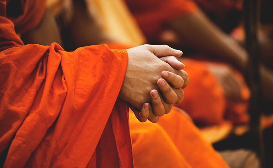 Buddhist monks in orange robes with clasped hands