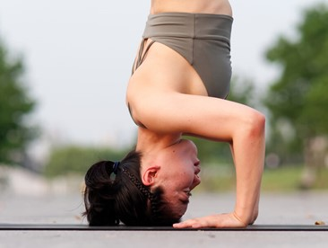 Side view of woman doing headstand on yoga mat