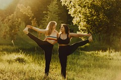 Two women with long hair doing yoga together in nature on a sunny day