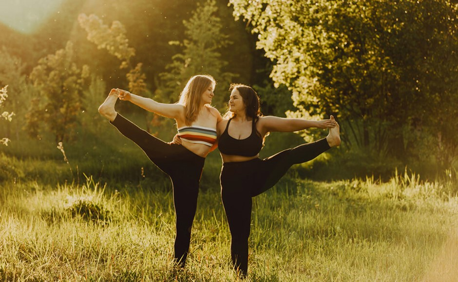 Two beautiful women with long hair doing yoga in nature on a sunny summer day