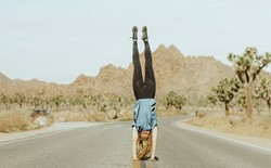 woman doing handstand in the middle of the road surrounded by joshua trees