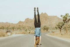 woman doing handstand in the middle of the road