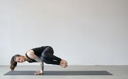 woman doing side crow yoga pose