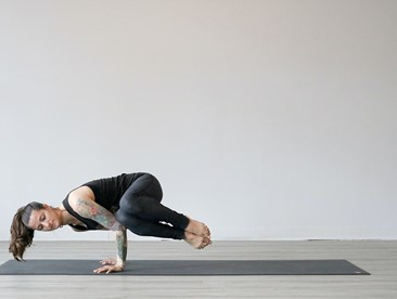 woman doing side crow yoga pose