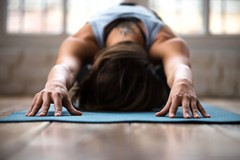 Woman doing yoga hare pose on mat in brick building