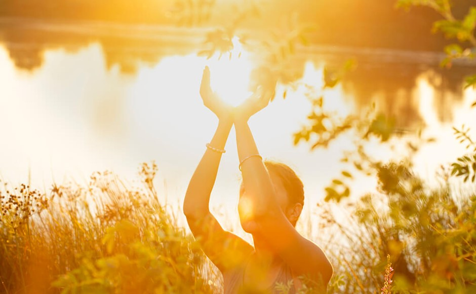 Woman hands in mudra like in the palm of hands, at sunset on the lake in nature