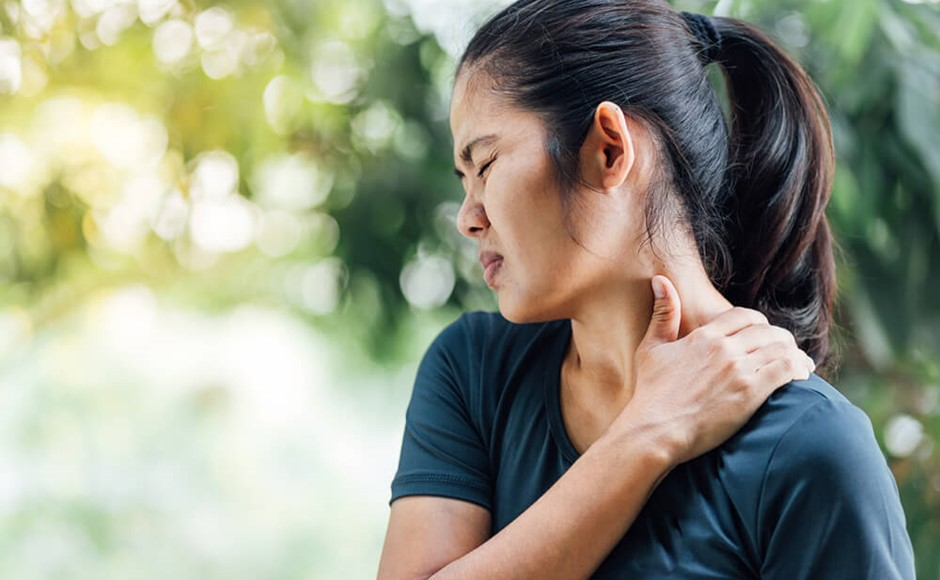 Woman holding side of her neck in pain