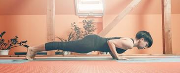 Woman practicing chaturanga in a yoga studio