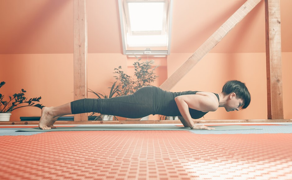Woman practicing chaturanga in a yoga studio