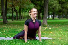 Woman practicing yoga asana of a Simhasana lion pose on green grass among trees in a summer park