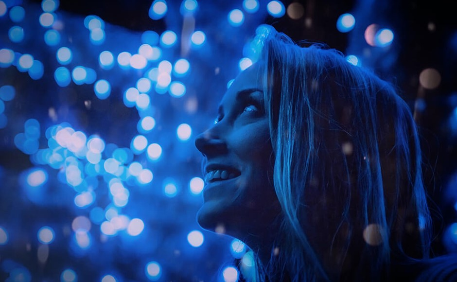 woman smiling in front of blue lights