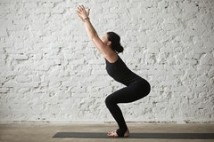 Young yogi woman in Utkatasana pose white loft background