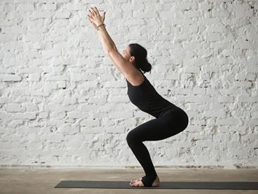 Young yogi woman in Utkatasana pose white loft background