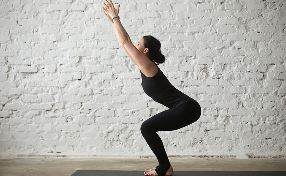 woman in black practicing Utkatasana chair pose with white background
